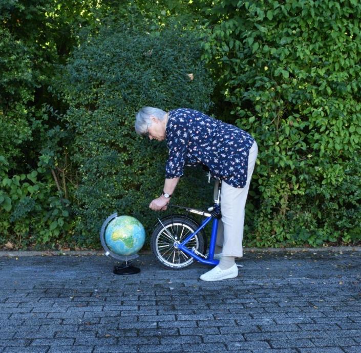 Bild einer Frau, die sich mit einem Globus und einem hintern Teil eines Laufrads posiert